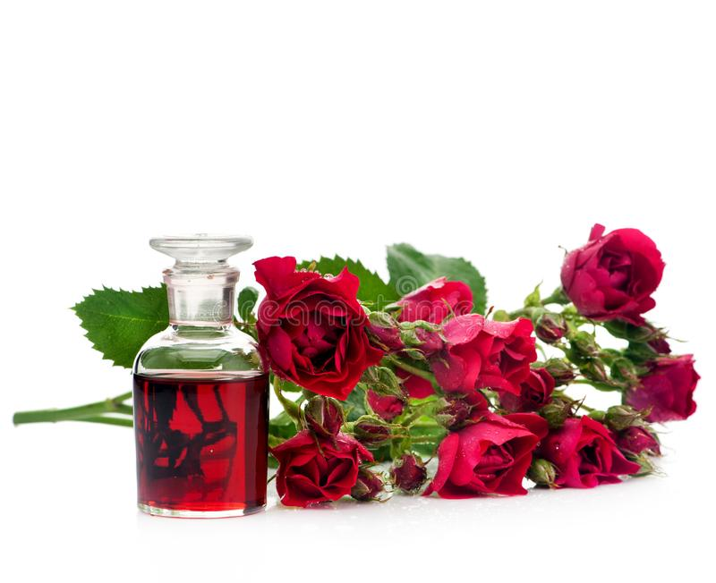 Huile essentielle de Rose dans une bouteille en verre et des roses de fleurs photo libre de droits