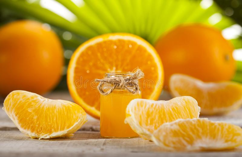 Huile essentielle orange sur le fond vert de feuilles image stock