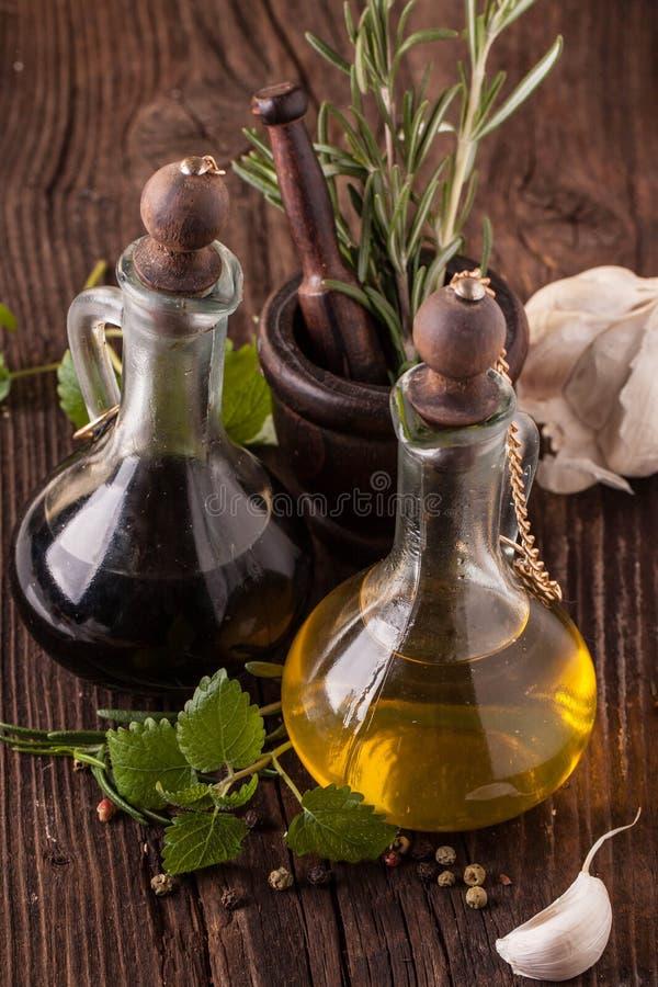Huile et vinaigre d'olive avec des herbes photographie stock libre de droits