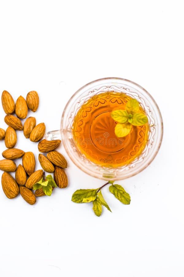 Huile salutaire et essentielle de badam ou amandes avec son th? salutaire dans une tasse transparente d'isolement photos stock