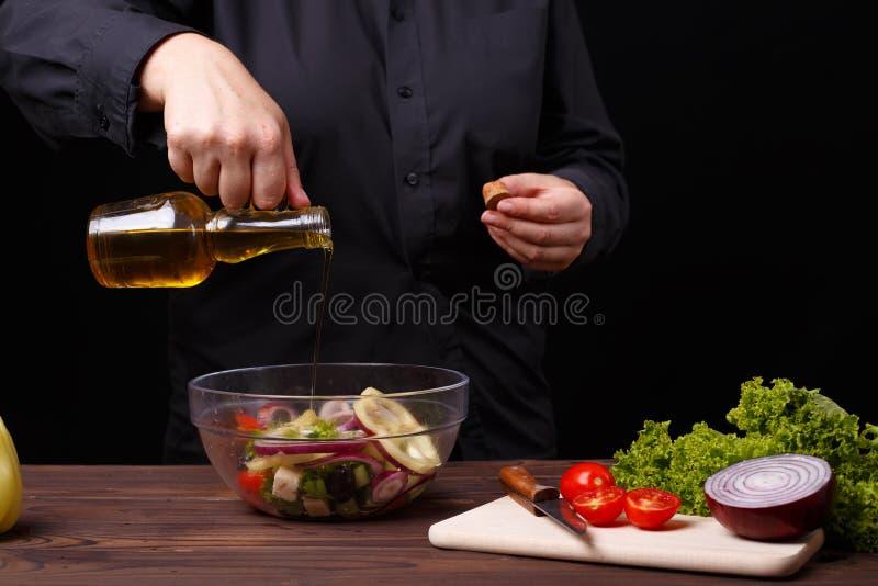 Huile se renversante de chef sur la salade grecque, procédé de cuisson, escroquerie de restaurant image stock