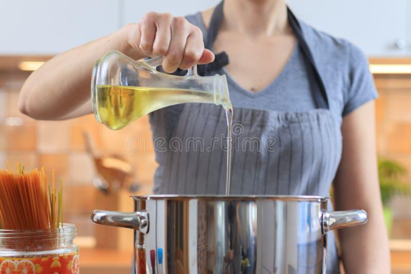 Huile se renversante de femme de pot dans la poêle dans la cuisine photographie stock libre de droits