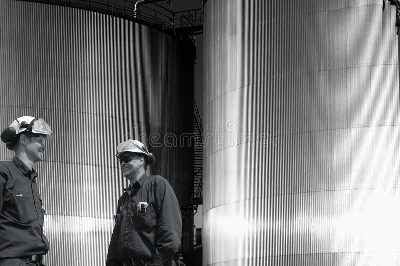 Huile-travailleurs et réservoirs de carburant industriels au crépuscule photos stock