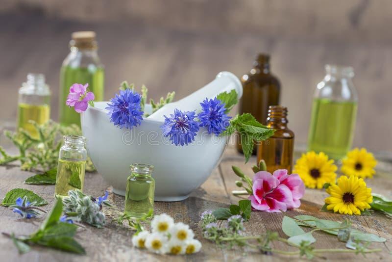 Huiles essentielles pour le traitement d'aromatherapy avec les herbes fraîches à l'arrière-plan de blanc de mortier images stock