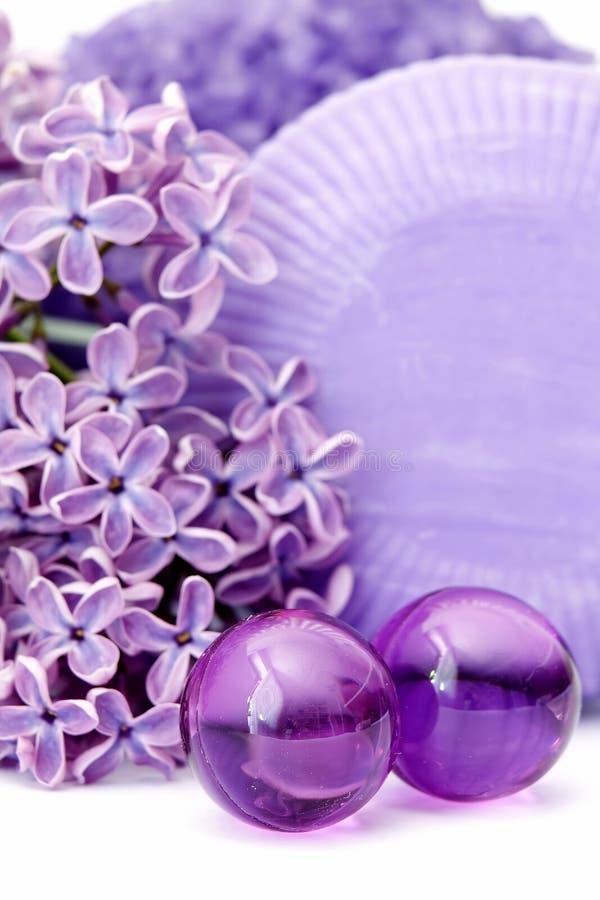 Huilez les perles de bain, le savon et les fleurs de lilas photographie stock libre de droits
