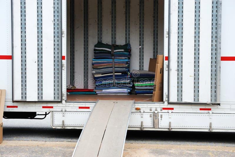 Huis bewegende vrachtwagen en het stapelen van meubilairstootkussens stock afbeelding