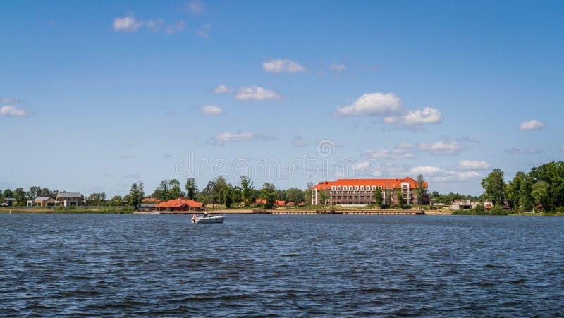 Huis bij het meerlandschap Polen stock afbeelding