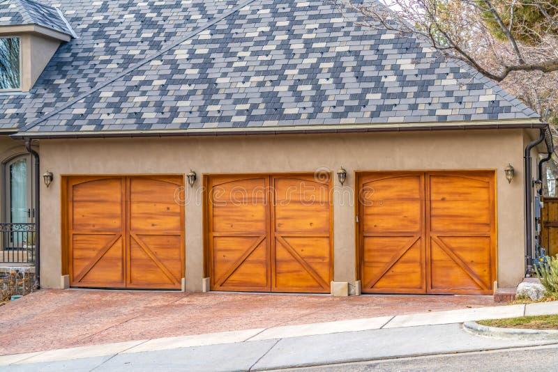 Huis buiten met grijs en wit dak en modieuze houten garagedeuren royalty-vrije stock afbeelding