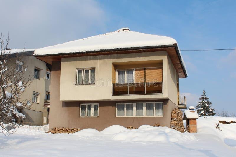 Huis in de voorsteden die met vers gevallen sneeuw op zonnige de winterdag wordt behandeld stock afbeelding