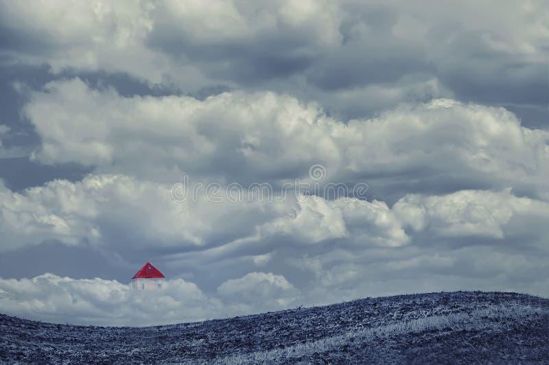 Huis in de wolken op een open gebied royalty-vrije stock afbeeldingen