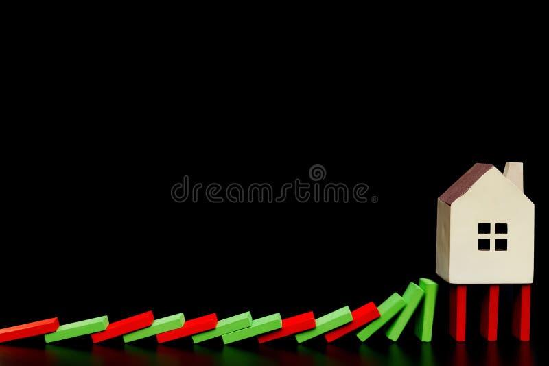 Huis die zich op dalende domino's op zwarte achtergrond bevinden als financieel concept royalty-vrije stock fotografie