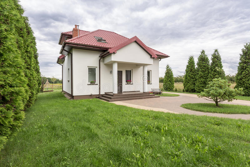 Huis door een tuin wordt omringd die stock afbeelding