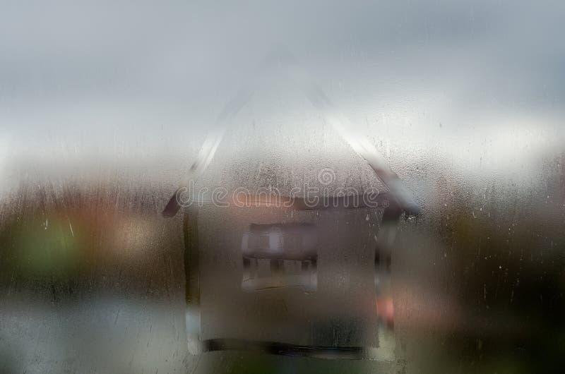 Huis in een nat venster royalty-vrije stock afbeelding