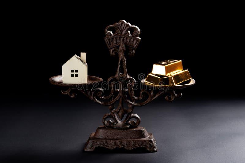 Huis en goudstaven op evenwichtige schaal stock foto