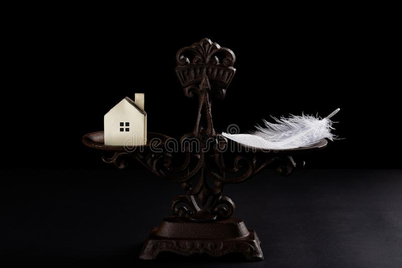 Huis en veer op evenwichtige schaal stock afbeelding