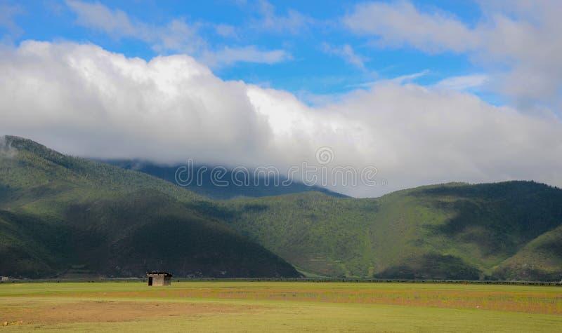 Huis, gras, berg en hemel in Yunnan, China stock afbeelding