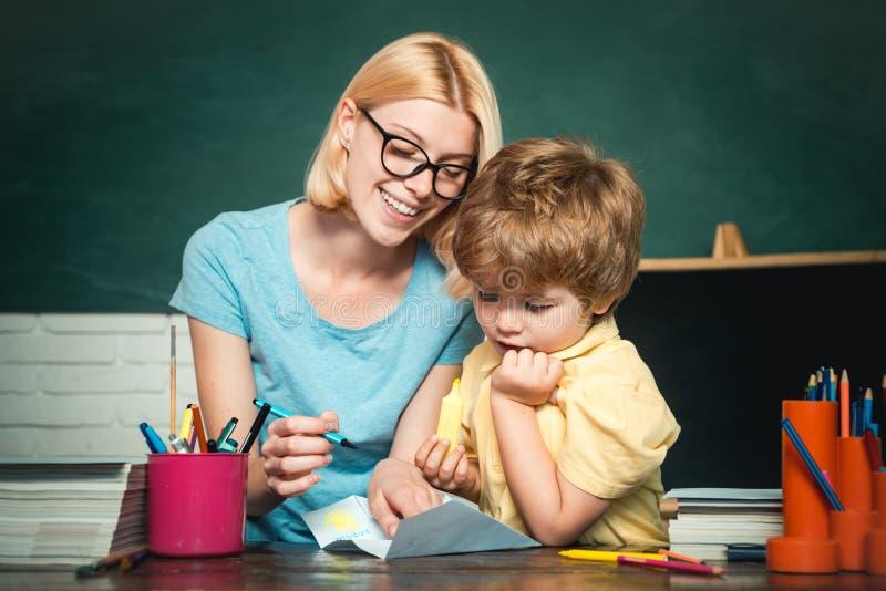 Huis het scholen of particuliere school Weinig klaar te bestuderen Klaar voor school Moeder die haar zoon in klaslokaal onderwijz royalty-vrije stock foto's