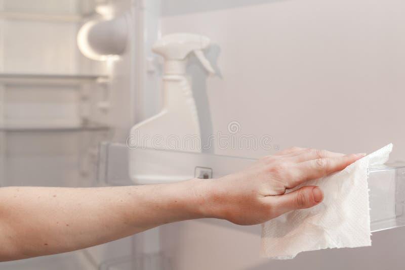 Huis het schoonmaken - nevelfles met detergentia voor het wassen van de koelkast De huishoudster veegt de planken van een schone  royalty-vrije stock foto's