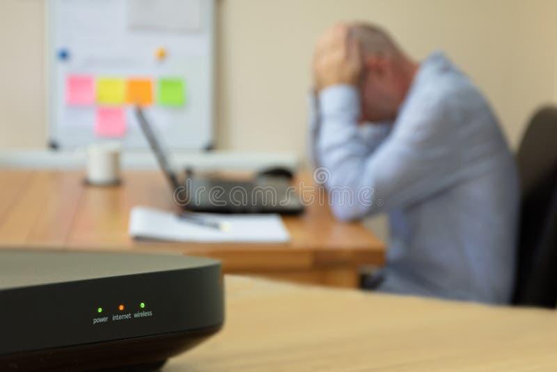 Huis het werk mens op computer bij verlies van Internet-signaal in Beccles, Suffolk, Engeland wordt geërgerd dat royalty-vrije stock afbeeldingen