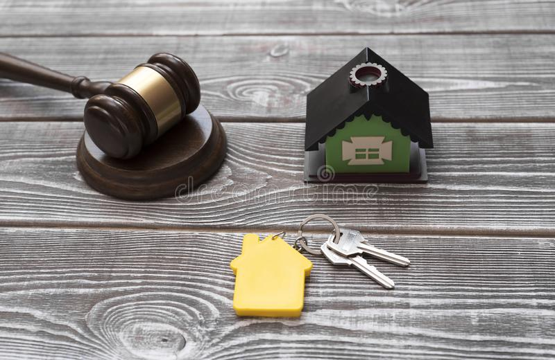 Huis, huissleutels met een sleutelring, rechtershamer op een houten achtergrond stock afbeeldingen