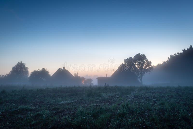 Huis in Lets platteland bij mistige avond stock foto's