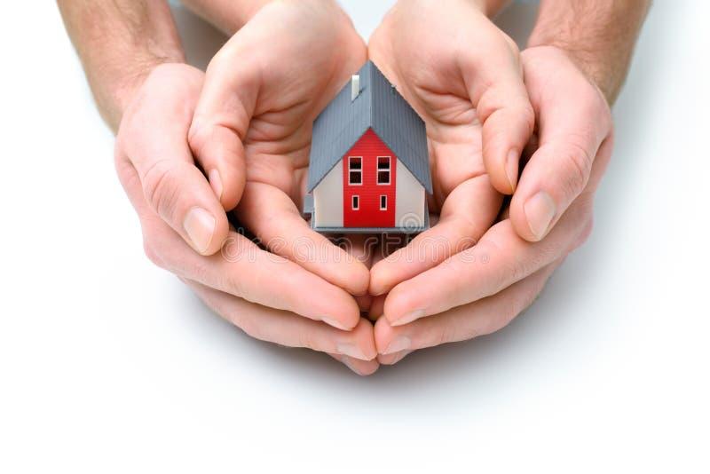 Huis in menselijke handen stock foto