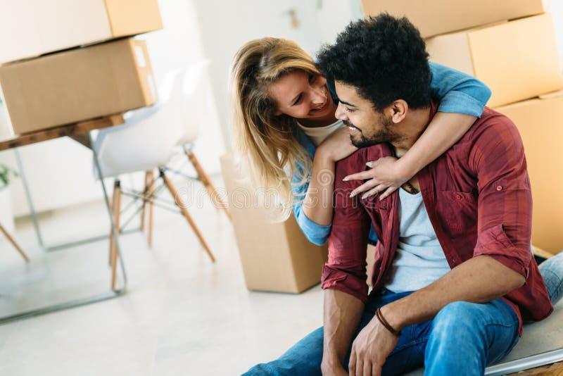 Huis, mensen, het bewegen zich en onroerende goederenconcept - gelukkig paar die pret hebben terwijl zich binnen het bewegen stock foto