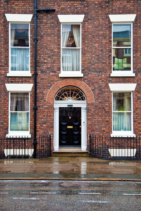 Huis met baksteenvoorzijde en deuropening stock afbeelding