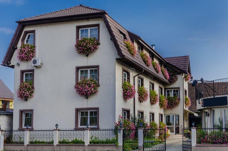 Huis met bloemen bij de vensters stock fotografie