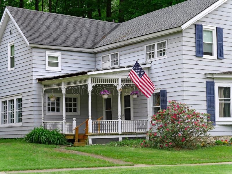 Huis met grote portiek en Amerikaanse vlag stock fotografie