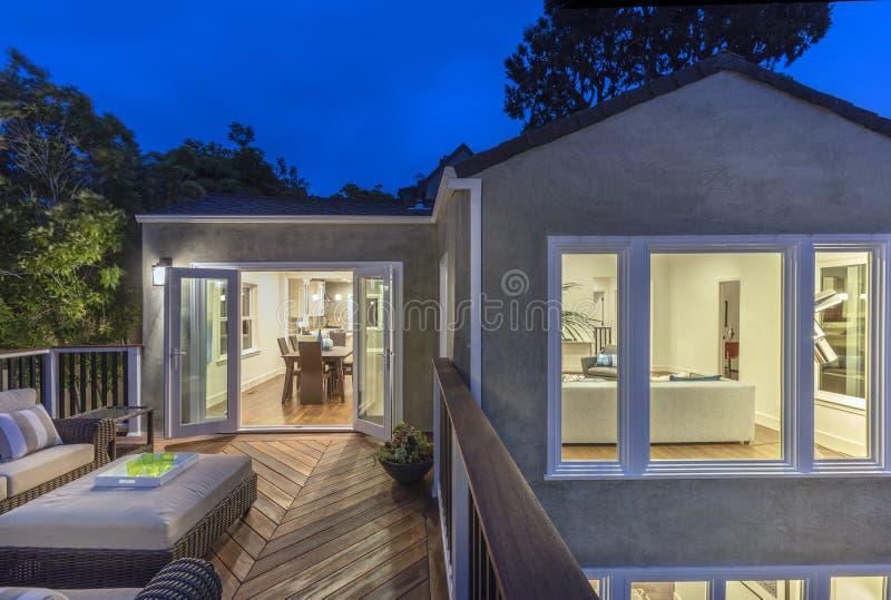Huis met meubilairterras/houten dek bij schemering stock afbeelding