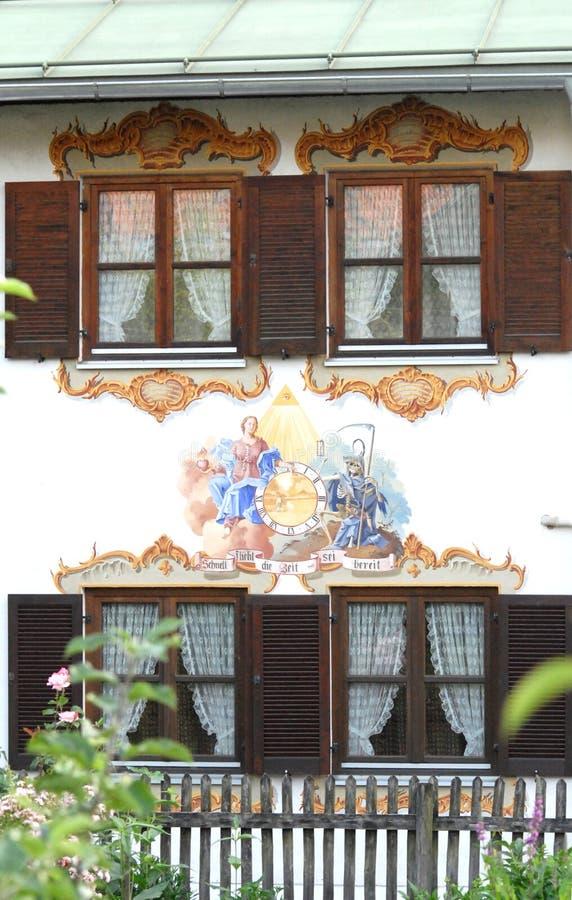Huis met vier vensters met mooie witte gordijnen, en een fresko in Oberammergau in Duitsland stock foto