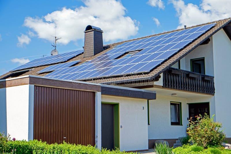 Huis met zonnepanelen stock afbeelding