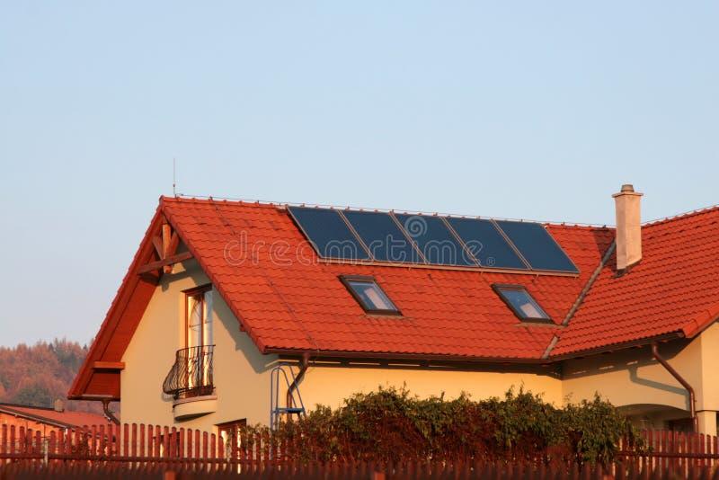 Huis met zonnepanelen op het dak voor water het verwarmen stock afbeelding