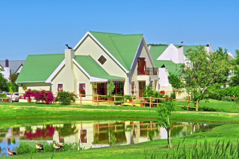 Huis naast meer en gazon royalty-vrije stock afbeeldingen