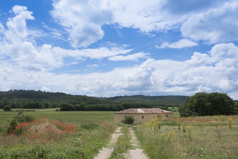 Huis onder blauwe hemel met de zomerbloemen in de voorgrond dichtbij Aix-en-Provence royalty-vrije stock fotografie