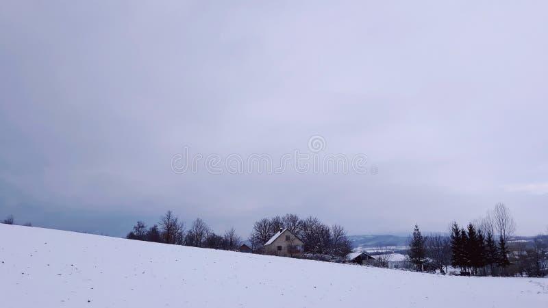 Huis op de dag van de de wintersneeuw stock foto's