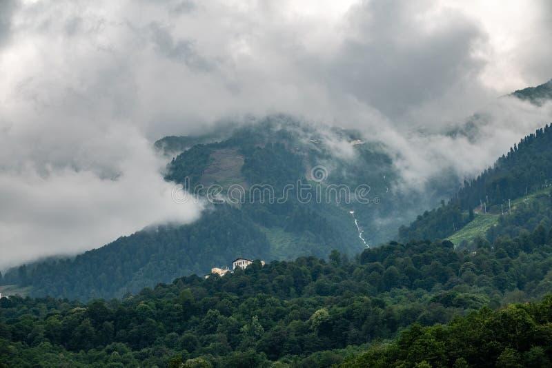 Huis op de helling van een hoge berg met een bosbergrivier op de helling stock afbeeldingen