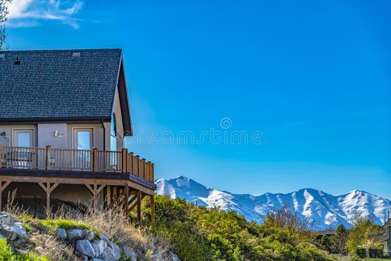 Huis op een heuvel met balkon die sneeuwberg en heldere blauwe hemel overzien royalty-vrije stock afbeeldingen