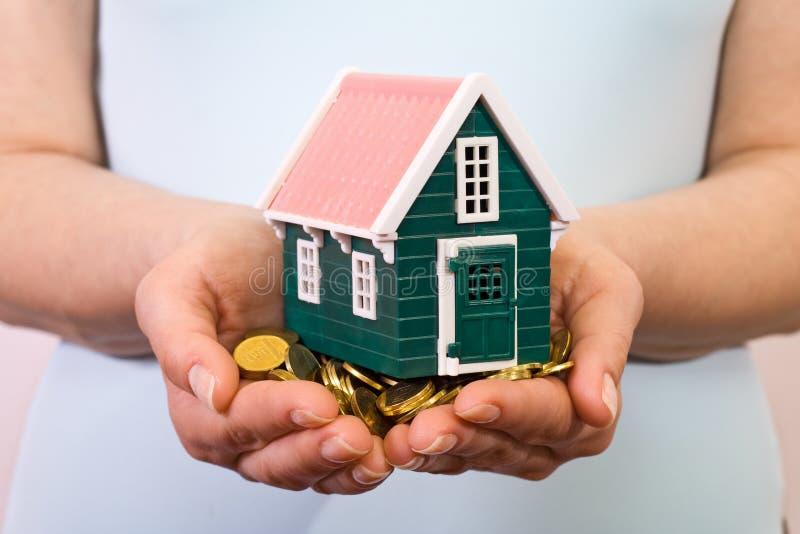 Huis op een stapel van geld in vrouwenhanden royalty-vrije stock afbeelding