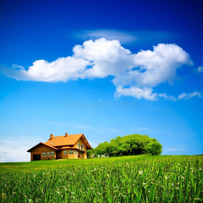 Huis op groen gebied stock foto