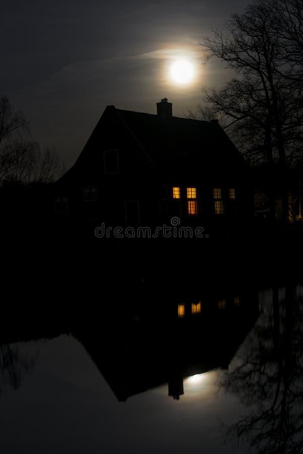 Huis, refelection en Maan stock foto