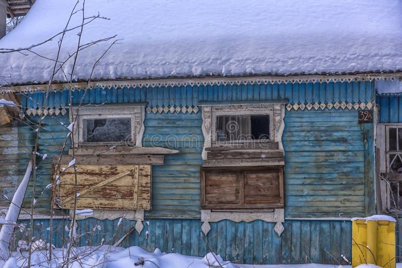 Huis snow-covered in de winter met ingescheept op vensters royalty-vrije stock afbeelding