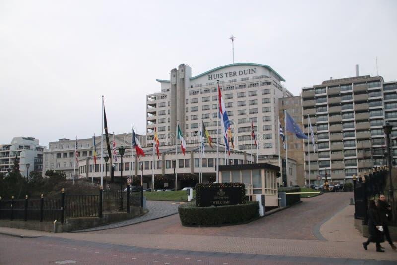 Huis ter duin, grote hotel en flats als hogere kringenplaats bij de kust in Noordwijk stock foto