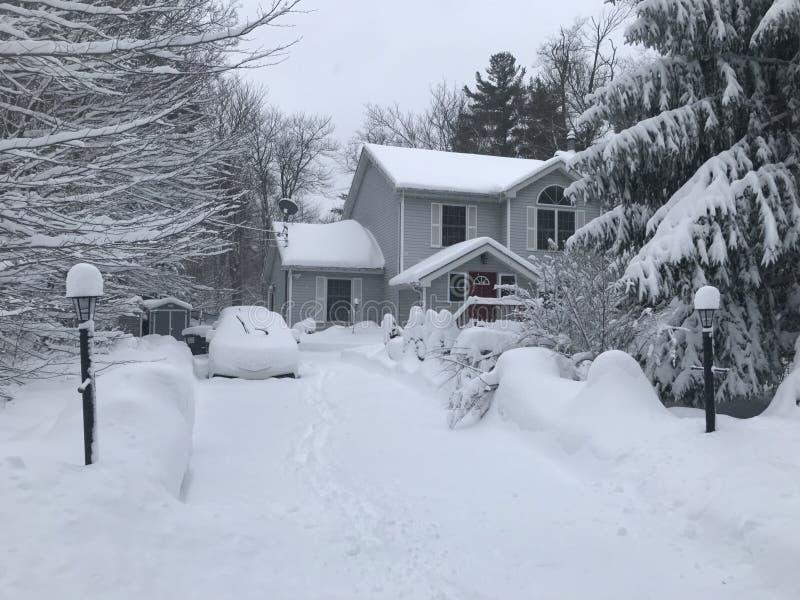 Huis tijdens de auto's van een sneeuwonweer in oprijlaan stock afbeeldingen