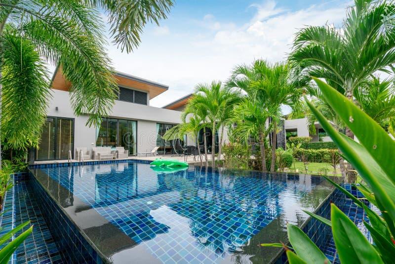 Huis of woningbouw Buiten en binnenlands ontwerp die tropische poolvilla met groene tuin tonen stock afbeeldingen