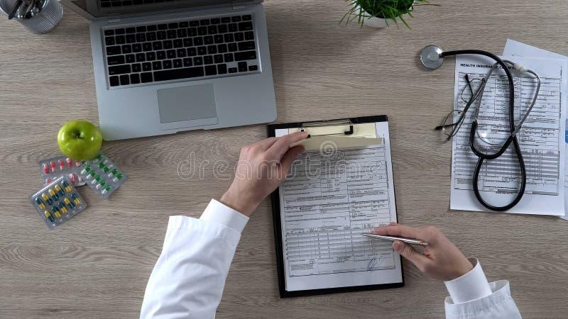Huisarts die voorschrift en ziektekostenverzekeringvorm, gezondheidszorghervorming ondertekenen stock afbeeldingen