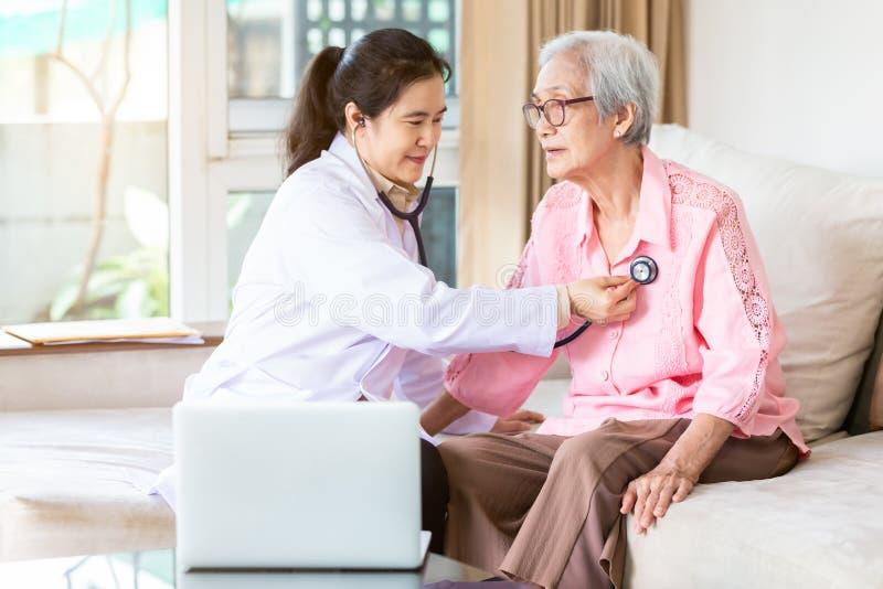 Huisarts of verpleegster die het glimlachen hogere geduldige gebruikende stethoscoop tijdens huisbezoek, jonge vrouwelijke huisve stock afbeelding