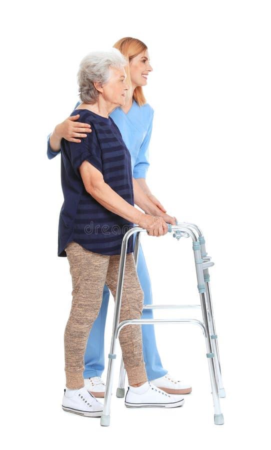 Huisbewaarder die bejaarde met het lopen kader helpen stock afbeeldingen