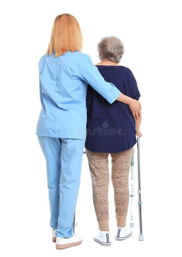 Huisbewaarder die bejaarde met het lopen kader op wit helpen royalty-vrije stock foto's